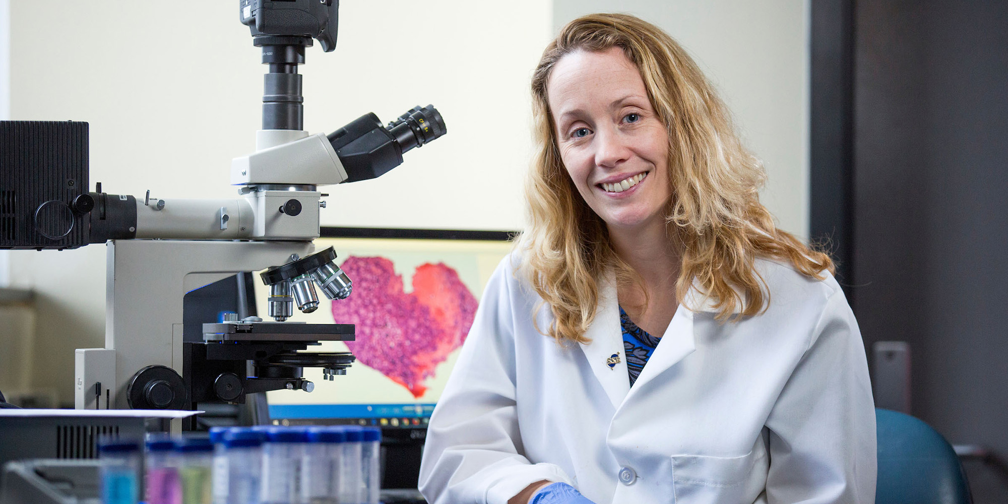 Aileen Keating seated by a microscope in a laboratory