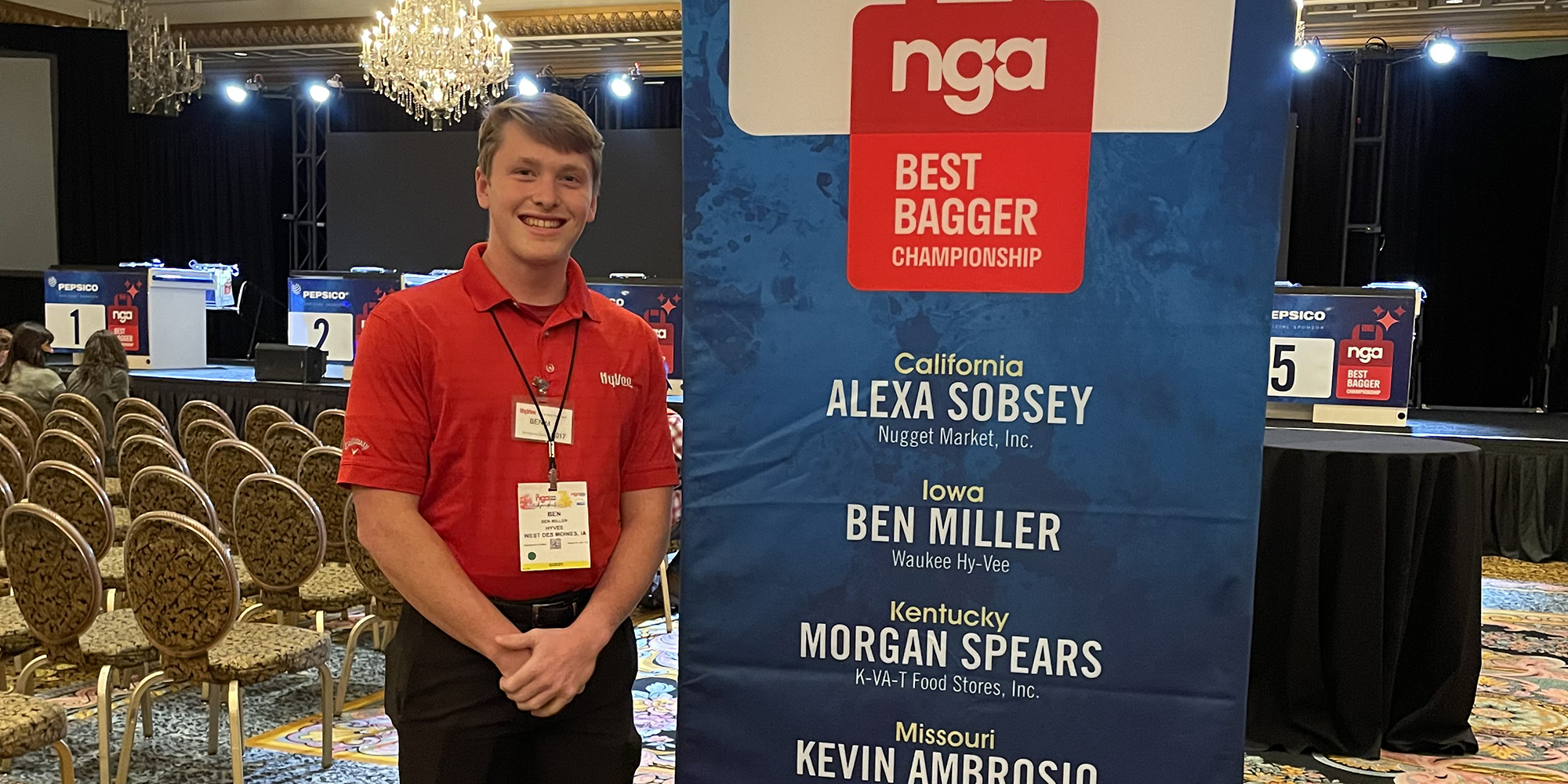 Ben Miller standing next to a banner listing the names of the National Grocers Association Best Bagger Championship