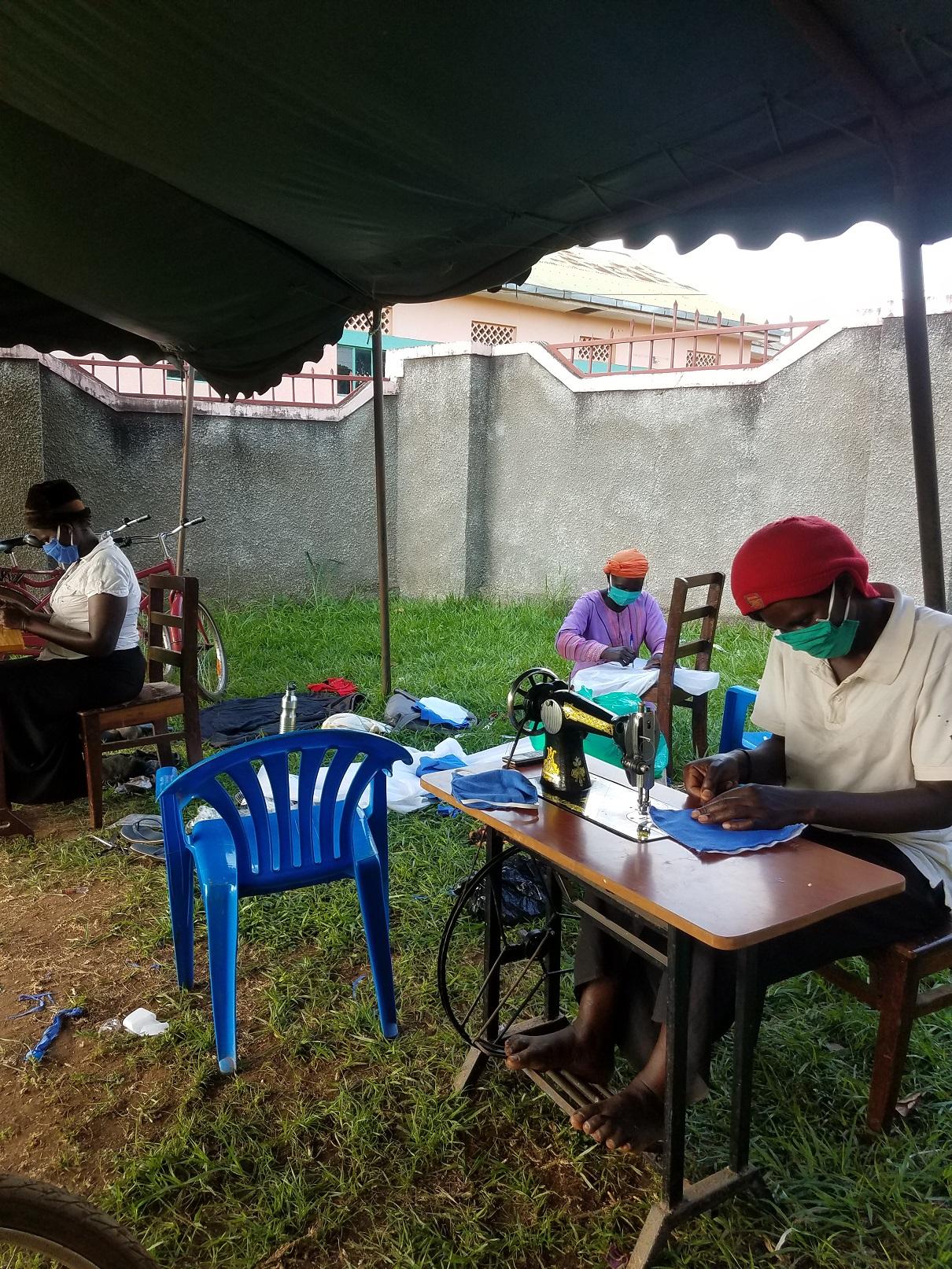 Ugandan women sewing under open air tent