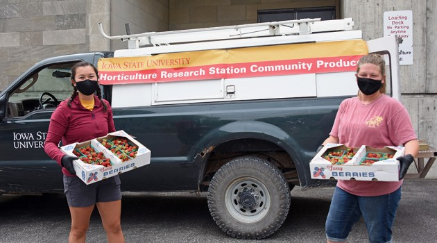 Tessa Dall and Alice Paulson holding boxes of strawberries