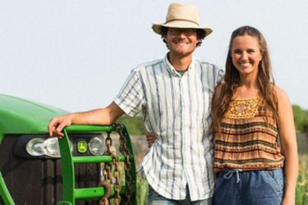 Male and female standing next to a tractor
