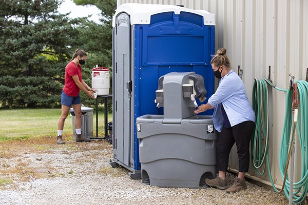Graduate students Alice Paulson, right, and Jean Yost use a rest and washing station at the Horticulture Research Station