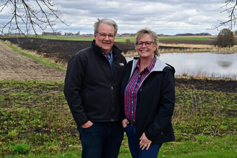 Eric and Kelly Hoien in front of recently burned prairie and wetland