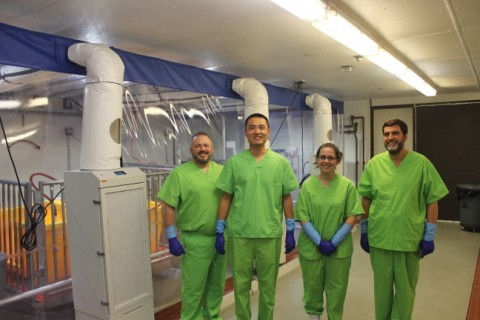 Four researchers standing inside specialized biocontainment facility