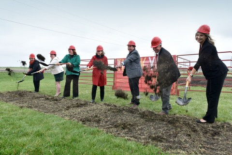 Individuals throwing shovels-full of dirt during groundbreaking ceremony