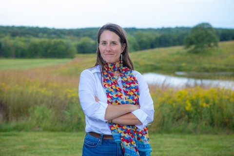 Lisa Schulte Moore, professor of natural resource ecology and management at Iowa State University, standing with her arms crossed in a grassy field.
