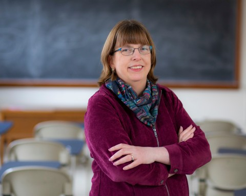 Nancy Boury standing in classroom with backdrop of chairs and chalkboard