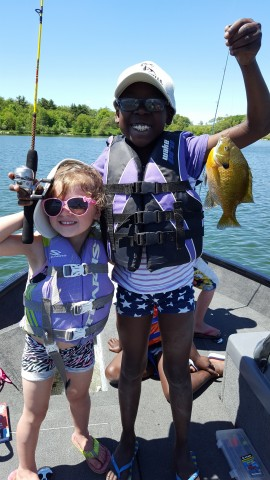 Two children holding fish with lake backdrop