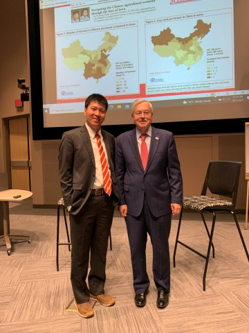 Wendong Zhang and former Iowa Governor Terry Branstad in front of PPT projection