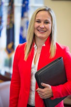Photo of Stephanie Carlson holding a portfolio in front of flags