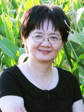 Dr. Kan Wang, headshot with plants in background