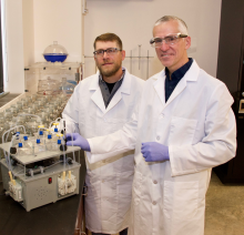 Two scientists in laboratory with screening tool on counter.