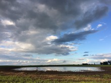 wet spot in farm field with cloudy sky above