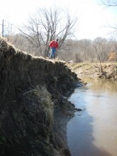 Man in red jacket standing on top of severely eroded streambank.