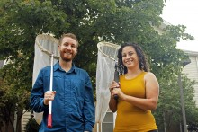 Colton Poore and Erika Ibarra-Garibay standing next to each other in front of a tree, holding nets used to capture bees