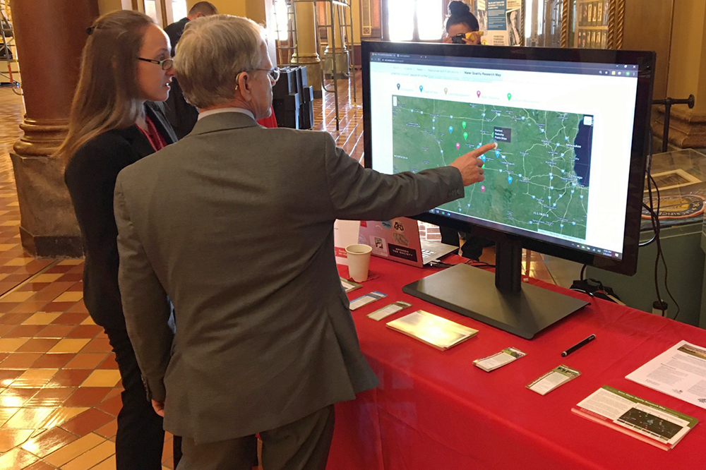 INRC Assistant Director and Iowa State Legislator review water quality map at ISU Day at the Capitol