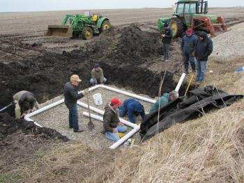 People installing blind inlet in farm field with farm equipment in background