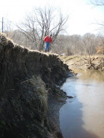 Man standing atop eroding streambank
