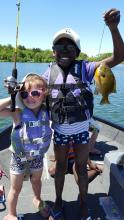 Two children holding fish and fishing gear in front of lake
